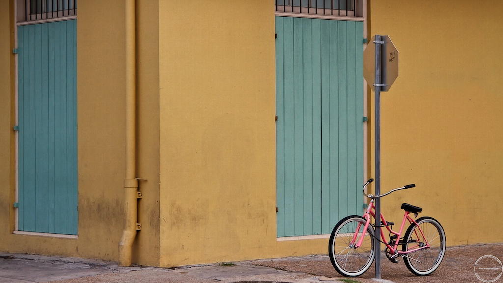 Pink bike against yellow building with blue doors