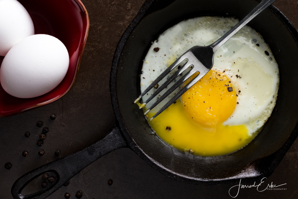 A rustic fried egg with a broken yolk in a cast iron skillet